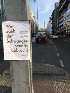 Plakataktion vom What the Fuck-Bündnis zu der Frage, wer eine Abtreibung zahlen muss. Hängt am Check-Point Charlie.