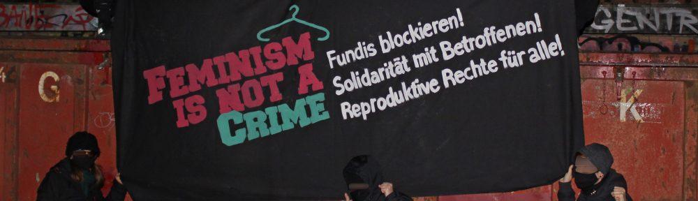 """Foto mit Aktivist:innen und Transpi mit der Aufschrift """"Feminism is not a crime"""""""