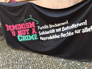 Foto von schwarzem Transpi mit der bunten Aufschrift: feminism is not a crime