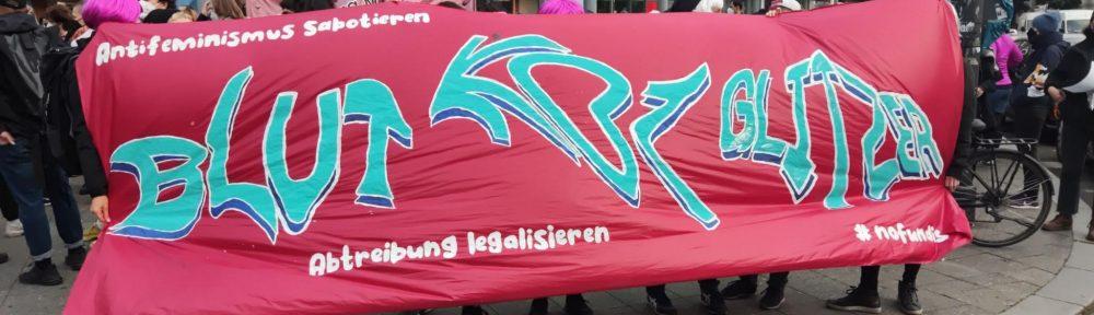 Foto des Fronttranspis der Demo. Auf dem Transp steht: Blut Kot Glitzer